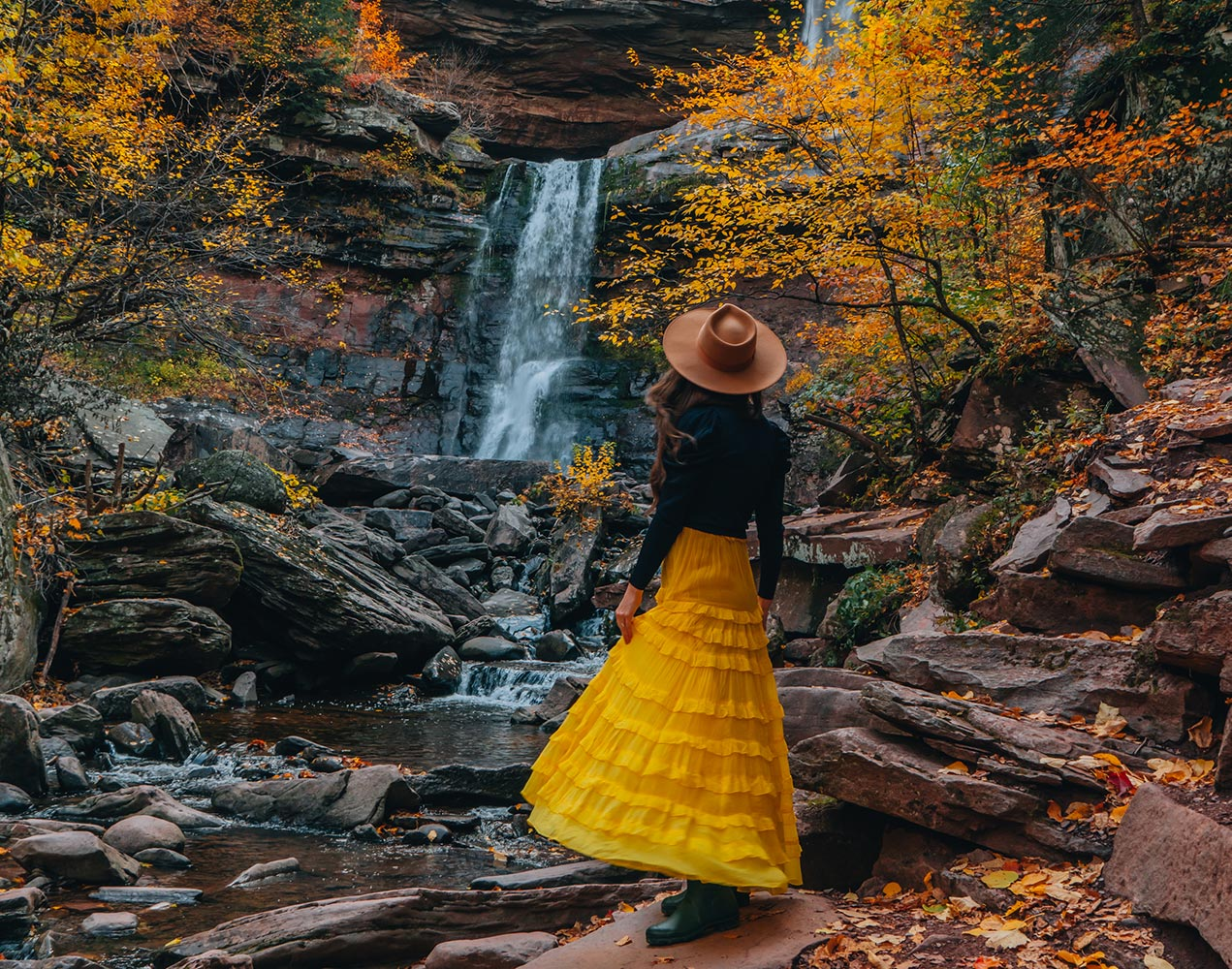 Woman Standing in Yellow Dress Boots a sweater and Hat in front of waterfall with fall foliage
