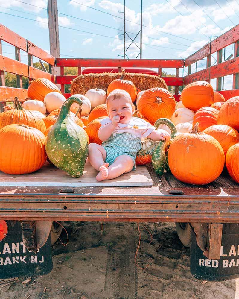 Baby sucking thumb in pumpkin truck