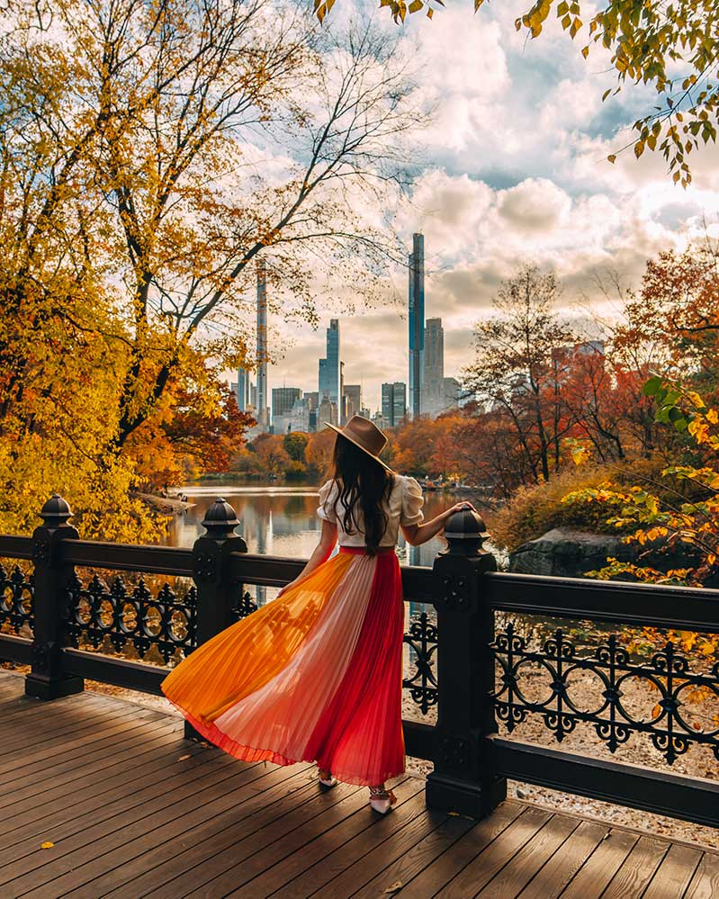 Kristi Hemric (Instagram: @khemric) poses on the Oak Bridge in Central Park surrounded by fall foliage and the NYC skyline