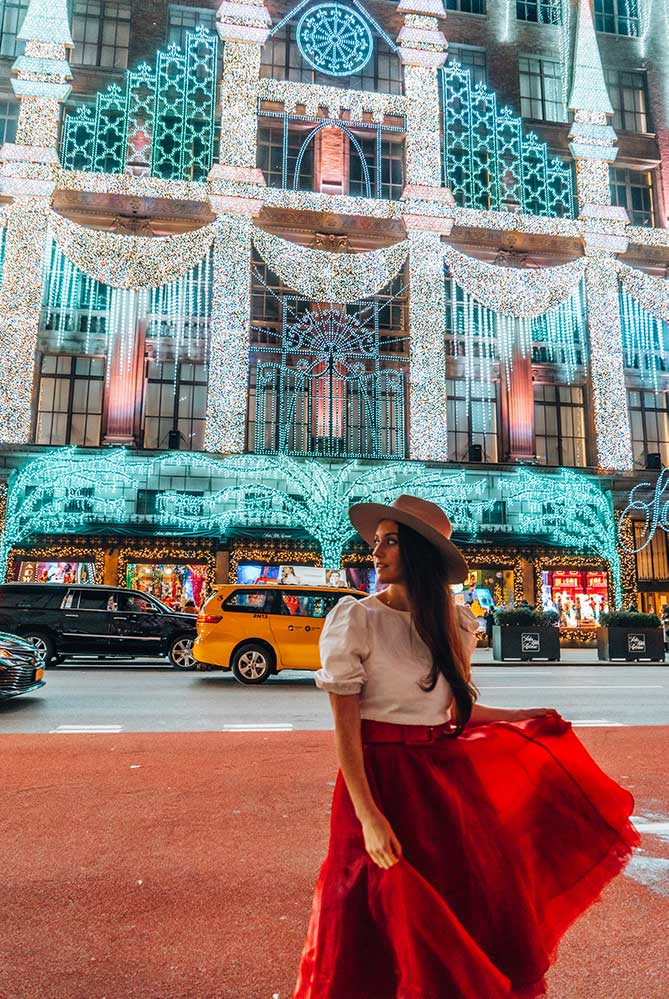 Kristi Hemric (Instagram: @khemric) crosses in front of the Saks Holiday Light Show on 5th ave in NYC